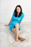 Glückliche Frau im Kleid sitzt auf weichem Teppich Lizenzfreies Stockbild