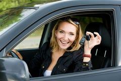 Glückliche Frau im neuen Auto mit Tasten Lizenzfreie Stockbilder