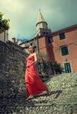 Glückliche Frau im Rot auf der alten Stadtstraße Stockfoto