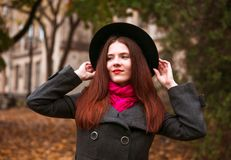 Glückliche Frau im schwarzen Hut gehend auf Herbststadtpark Regnerisches Wetter und gelbe Bäume herum Stockbilder