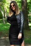 Glückliche Frau im schwarzen Kleid und Lederjacke und Sonnenbrille, die in der Natur an einem sonnigen Frühlingstag mit der Hand  stockfotografie