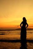 Glückliche Frau im Sonnenuntergang am Strand in Thailand Stockfoto
