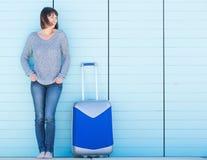Glückliche Frau im Urlaub, die mit Koffer lächelt lizenzfreies stockfoto