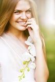 Glückliche Frau im weißen Kleid mit Orchidee Stockbilder