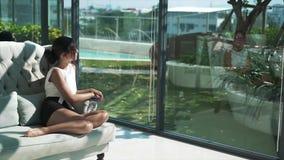 Glückliche Frau ist auf Couch und Lesebuch entspannend stock video