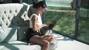 Glückliche Frau ist auf Couch und mit Laptop entspannend stock footage