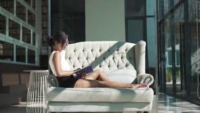 Glückliche Frau ist auf Sofa und dem Ablesen eines Buches entspannend stock video footage