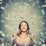 Glückliche Frau jubelt die pumpenden ekstatischen Fäuste feiert Erfolg unter einem Geldregen stockbild