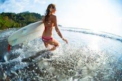 Glückliche Frau läuft in Ozean stockfotografie