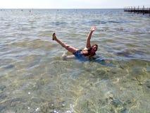 Glückliche Frau liegt im Meer Stockbilder