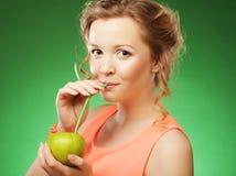 Glückliche Frau mit Apfel und Stroh-Cocktail, grüner Hintergrund Lizenzfreies Stockbild