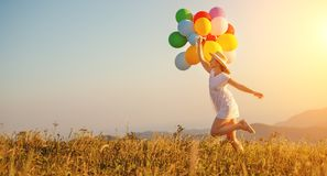 Glückliche Frau mit Ballonen bei Sonnenuntergang im Sommer stockfoto