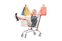 Glückliche Frau mit Beuteln in einem Einkaufswagen Stockfoto