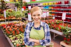 Glückliche Frau mit Blumen im Gewächshaus Stockfotos
