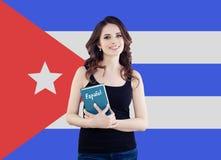 Glückliche Frau mit Buch gegen den Kuba-Flaggenhintergrund Lernen Sie spanische Sprache stockbilder