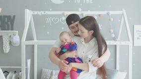 Glückliche Frau mit dem Baby, welches die Umarmungen des Ehemanns genießt stock footage