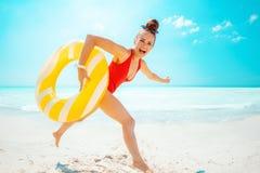 Glückliche Frau mit dem gelben aufblasbaren Rettungsring, der Spaßzeit hat stockfotos