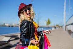Glückliche Frau mit dem Lachen vieler Einkaufstaschen stockfoto