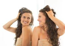 Glückliche Frau mit dem langen nassen Haar, das im Spiegel schaut Lizenzfreies Stockfoto