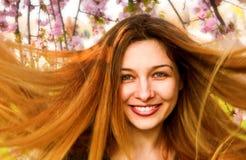 Glückliche Frau mit dem schönen langen Haar und den Blumen Lizenzfreie Stockfotografie