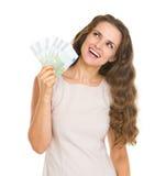 Glückliche Frau mit den Euros, die oben auf Kopienraum schauen Stockfotografie