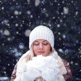 Glückliche Frau mit den geschlossenen Augen, die Schnee anhalten Lizenzfreies Stockfoto
