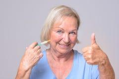 Glückliche Frau mit der Einspritzung, die sich Daumen zeigt Stockfoto