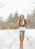 Glückliche Frau mit der Schale des Heißgetränks gehend in Winterpark Lizenzfreies Stockfoto