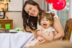 Glückliche Frau mit der Tochter, die Geburtstags-Kuchen isst Stockbild