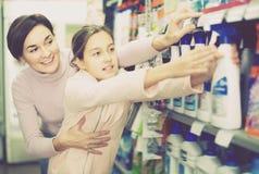 Glückliche Frau mit der Tochter, die Reiniger wählt lizenzfreies stockfoto