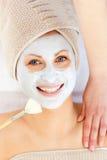 Glückliche Frau mit einer Lehmschablone auf ihrem Gesicht Stockfoto