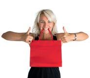 Glückliche Frau mit Einkaufstasche im Mund und im Zeigen des okayzeichens Lizenzfreies Stockfoto