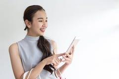 Glückliche Frau mit Einkaufstasche und Handy Macht das on-line-Einkaufen auf einer Tablette stockbild