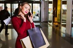 Glückliche Frau mit Einkaufstaschen im Einkaufszentrum Telefon Stockfotos