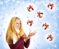 Glückliche Frau mit fallendem Weihnachtsgeschenk Lizenzfreie Stockfotos