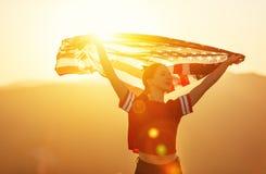 Glückliche Frau mit Flagge von Vereinigten Staaten den Sonnenuntergang auf Na genießend stockbilder