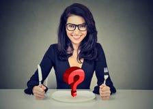 Glückliche Frau mit Gabel und Messer, das bei Tisch mit leerer Platte sitzt Lizenzfreie Stockfotos