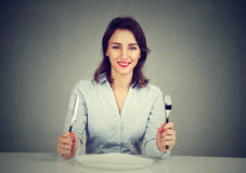 Glückliche Frau mit Gabel und Messer, das bei Tisch mit leerer Platte sitzt Lizenzfreie Stockbilder