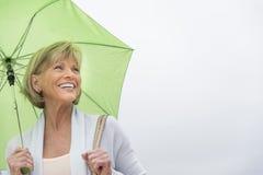 Glückliche Frau mit grünem Regenschirm gegen klaren Himmel Lizenzfreies Stockfoto