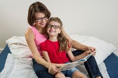 Glückliche Frau mit ihrem Tochterkind, ein Buch a zusammen lesend Stockfotos