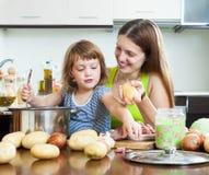 Glückliche Frau mit Kinderdem kochen Stockfoto