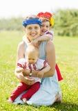 Glückliche Frau mit Kindern in der russischen Volkskleidung Lizenzfreie Stockfotos