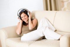 Glückliche Frau mit Kopfhörern auf Sofa im Aufenthaltsraum lizenzfreies stockfoto