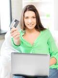 Glückliche Frau mit Laptop-Computer und Kreditkarte Lizenzfreies Stockfoto