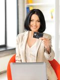 Glückliche Frau mit Laptop-Computer und Kreditkarte Stockfotos