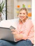 Glückliche Frau mit Laptop-Computer und Kreditkarte Lizenzfreie Stockfotografie