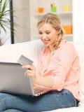Glückliche Frau mit Laptop-Computer und Kreditkarte Stockfoto
