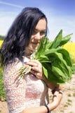 Glückliche Frau mit Maiglöckchen in den Händen lizenzfreie stockbilder