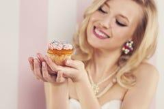 Glückliche Frau mit Muffin lizenzfreie stockfotos