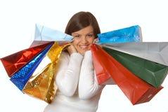 Glückliche Frau mit multi farbigen Einkaufenbeuteln Stockfotografie